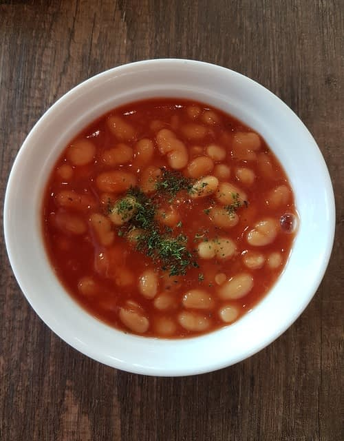 Baked beans and fresh herbs in a white bowl on wood background