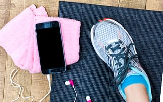 Grey trainers on black exercise mat on wooden floor next to black phone with earphones and pink towel