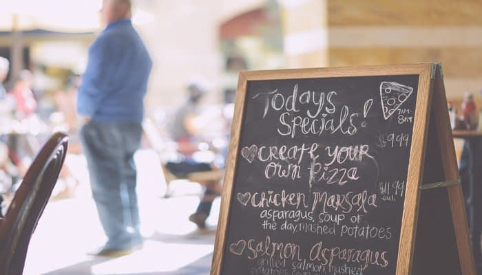 Price anchors on a restaurant specials blackboard in a square including create your own pizza and chicken marsala
