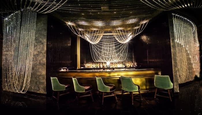 Gold drinks bar with chandelier lights  and green velvet chairs