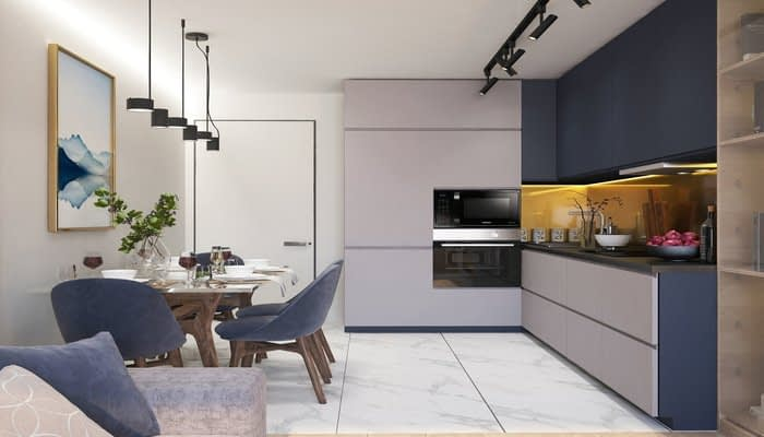Grey and navy blue kitchen with directional lights and dining table to one side with pendant lighting