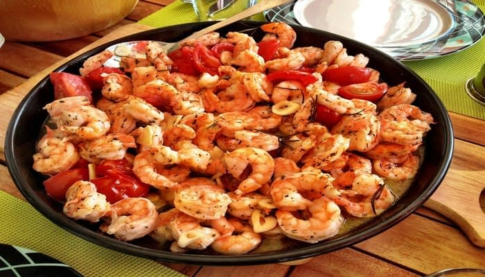 Cooked king prawns and tomatoes in black dish