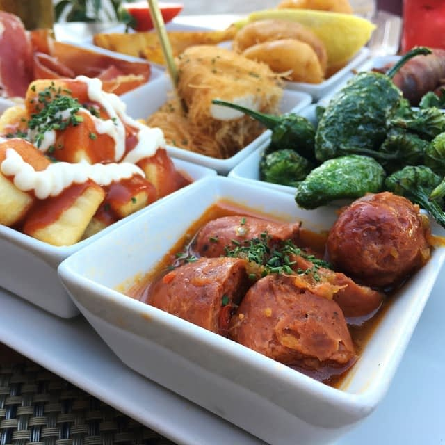 White tapas dishes of peppers, patatas bravas and chorizo