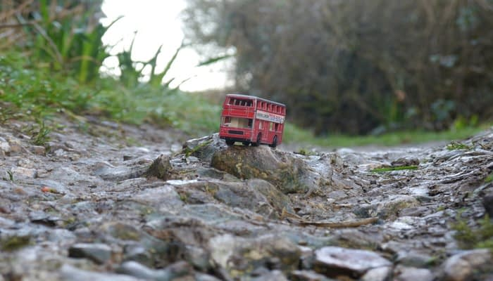 toy red double decker bus on a rocky path