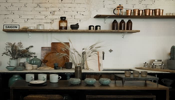 Dark wood kitchen with white brick wall and cluttered shelves using rule of three