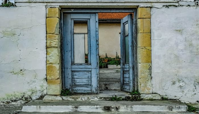 Blue aged wooden doors outside in white stone wall with steps