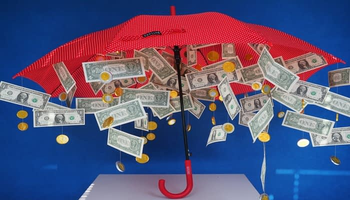 Banknotes raining down from red umbrella