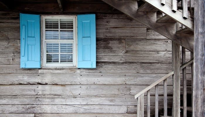 Window with blue shutters on the side of wooden house