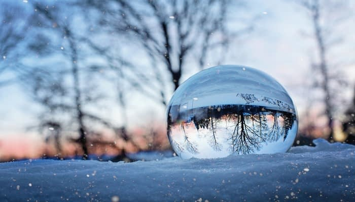 Crystal ball in the snow with upside down reflection of trees