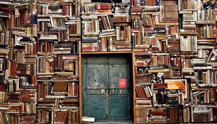 Double doors surrounded by books floor to ceiling