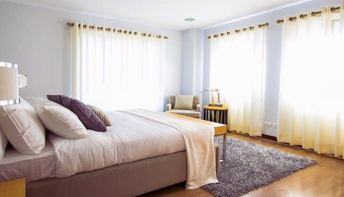 Double bedroom with three large windows light curtains and grey rug on wooden floor