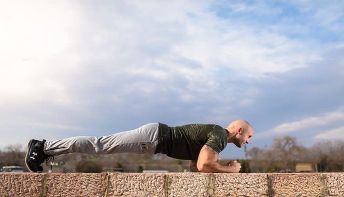 Man demonstrating plank exercise  in Under Armour sports clothing