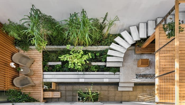 Internal courtyard with stone steps, wooden deck balcony and planters and garden furniture