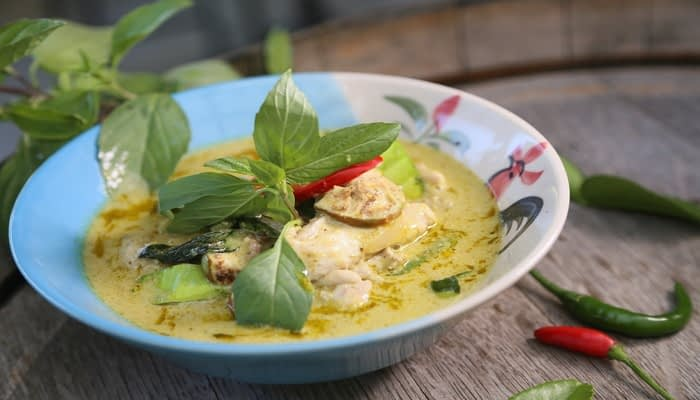 Thai green curry with chicken and chillis in painted bowl on wooden table