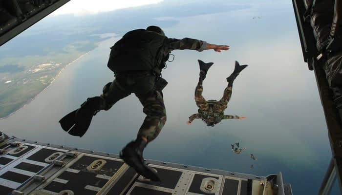 Soldiers in camo and flippers skydiving from an airplane cargo hold over a lake
