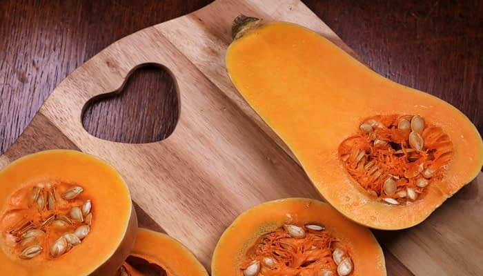 Two butternut squash cut in halves on wooden chopping board