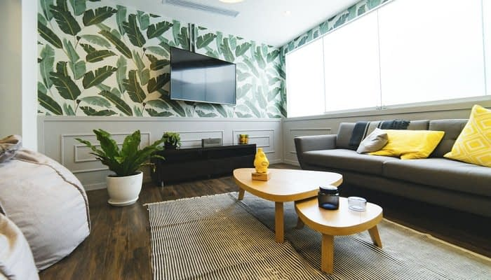 Grey lounge with large windows, leaf pattern wallpaper and yellow cushions