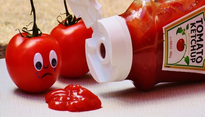 Heinz tomato ketchup puddle next to open bottle and tomato with crying face drawn on
