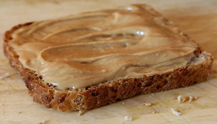 peanut butter on slice of brown bread