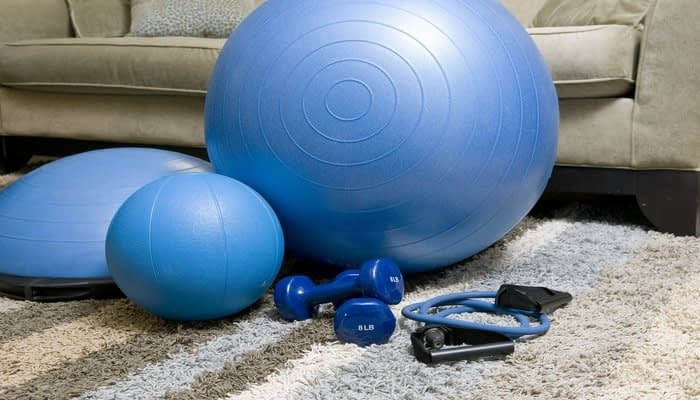 Blue medicine ball, skipping rope and barbells on carpet by sofa