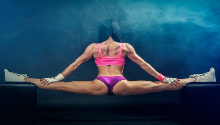 Bodybuilder doing the splits with back to camera in pink sports bra and purple briefs