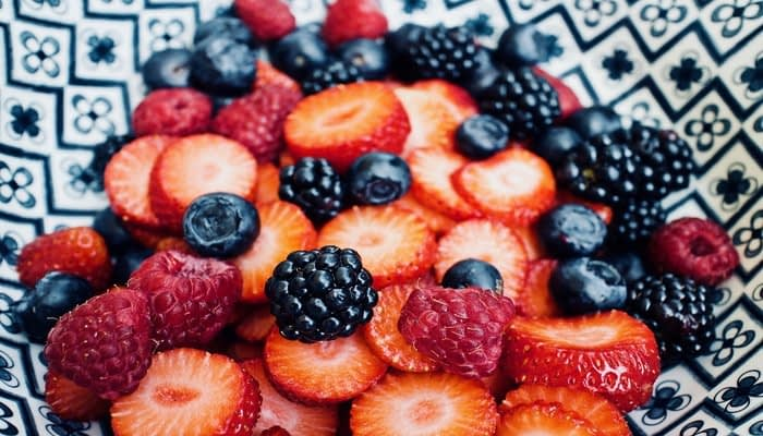 blueberries, blackberries, raspberries and sliced strawberries in patterned bowl