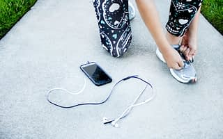 Runner in black patterned leggings kneeling on a path and tying their running trainer shoelaces with phone and earphones on the ground