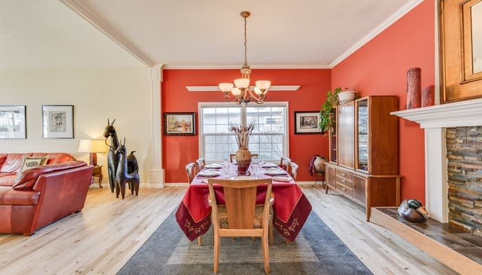 Dining room with red painted walls, stone fireplace, wooden floors and rug