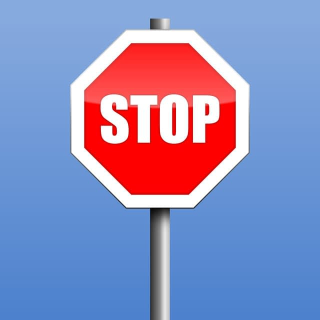 red and white stop sign on blue background