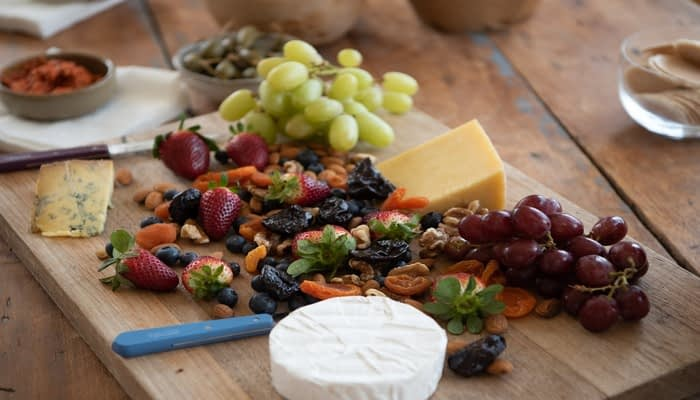 Wooden serving board with cheddar, blue cheese, grapes, mixed nuts and strawberries