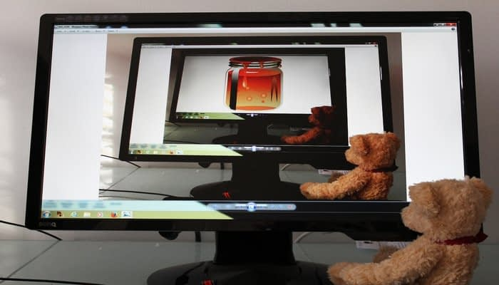 cuddly toy bear looking at honey jar on computer screen