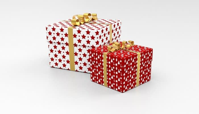 Two boxes wrapped in red and white gift paper with gold bows