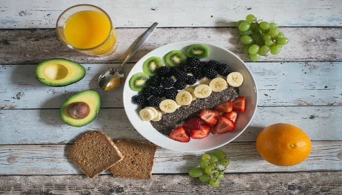 Rows of kiwi, blackberries, sliced banana, chia and strawberries in a bowl on table with orange juice, avocado, grapes, brown bread and orange to represent superfoods