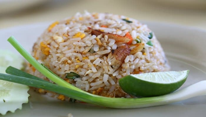 Egg fried rice in upside down bowl shape on white plate with lime spring onion garnish