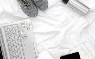 Grey trainers, silver drinks bottle, black phone and silver laptop on white bedsheet
