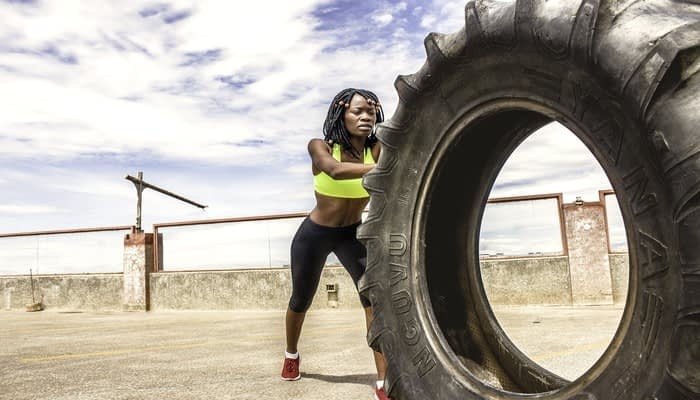 Woman with braids in yellow sports bra and black leggings pushing lorry tyre