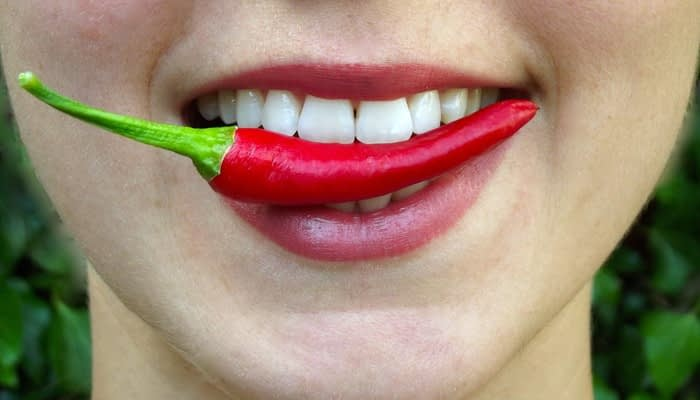 Red chilli pepper held in someone's teeth.