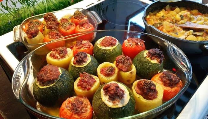 Two clear dishes of stuffed peppers and stuffed squash