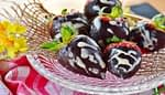 Chocolate dipped strawberries with white icing in a glass dish