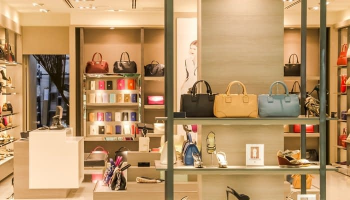 Shelves of handbags and shoes in fashion shop